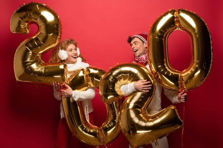 Photo for Smiling couple in winter outfit holding new year 2020 golden balloons, on red - Royalty Free Image