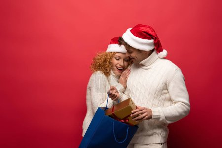Photo for Happy couple in santa hats with present in shopping bag, isolated on red - Royalty Free Image