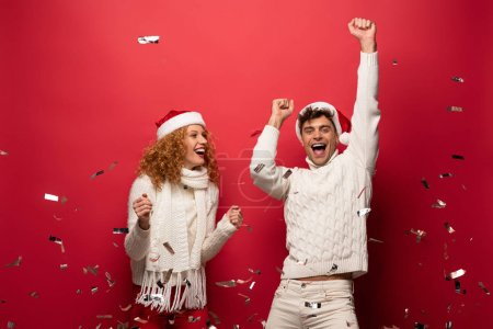 Photo for Happy couple in santa hats celebrating with golden confetti, isolated on red - Royalty Free Image