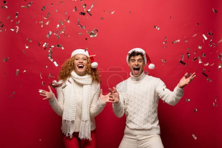 Photo pour Excité couple dans santa chapeaux crier et célébrer avec des confettis dorés, isolé sur rouge - image libre de droit