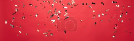Photo for Panoramic shot of christmas golden confetti isolated on red - Royalty Free Image