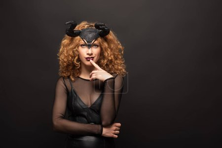 Photo pour Beautiful pensive woman posing in halloween costume with horns on black - image libre de droit