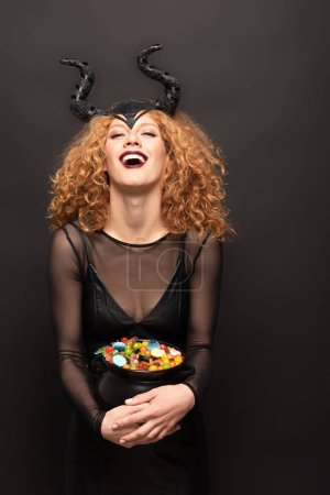 Photo pour Beautiful laughing woman in maleficent costume holding pot with candies for halloween on black - image libre de droit