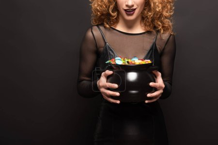 Photo pour Vue recadrée de femme tenant pot avec des bonbons pour Halloween sur noir - image libre de droit