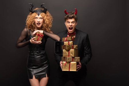 Photo pour Un couple inquiet posant en costumes d'halloween avec des boîtes cadeaux sur noir - image libre de droit