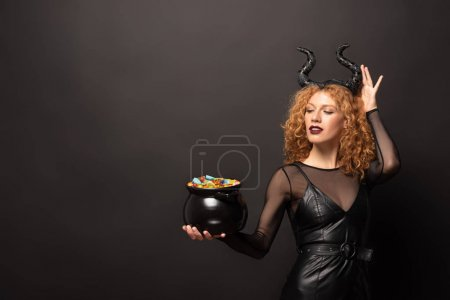 Photo pour Attractive woman in maleficent costume holding pot with bonbons for halloween on black - image libre de droit
