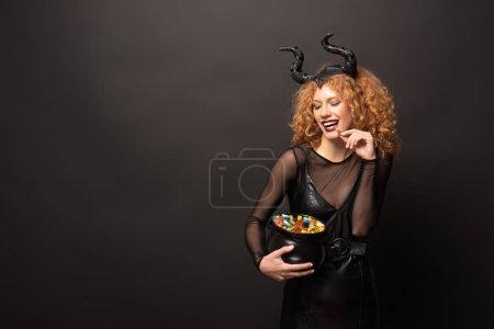 Photo pour Belle femme en costume maléfique tenant un pot avec des bonbons pour l'halloween sur noir - image libre de droit