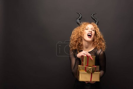 Photo pour Laughing woman in maleficent costume holding presents for halloween on black - image libre de droit
