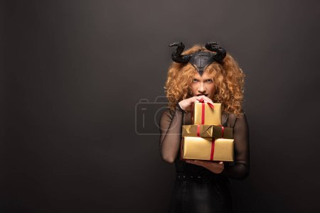 Photo pour Femme effrayante en costume fantastique tenant des boîtes-cadeaux pour l'halloween sur noir - image libre de droit