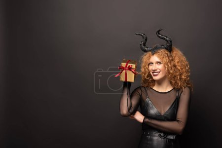 Photo pour Smiling curly woman in maleficent costume holding gift box for halloween on black - image libre de droit