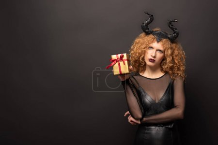 Photo pour Beautiful curly woman in maleficent costume holding gift box for halloween on black - image libre de droit