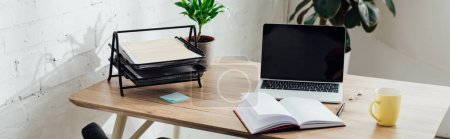 Photo for Notebook, laptop with blank screen and cup on working table, panoramic shot - Royalty Free Image