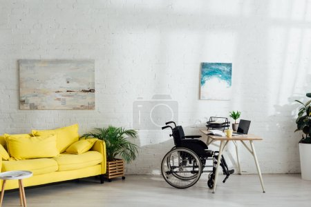 Interior of living room with workplace and wheelchair by table