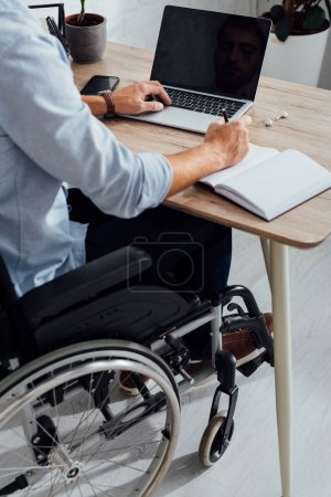 Photo for Cropped view of man in wheelchair writing in notebook and using laptop at desk - Royalty Free Image