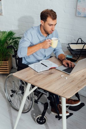 Photo for Man in wheelchair using laptop and drinking coffee at workplace - Royalty Free Image