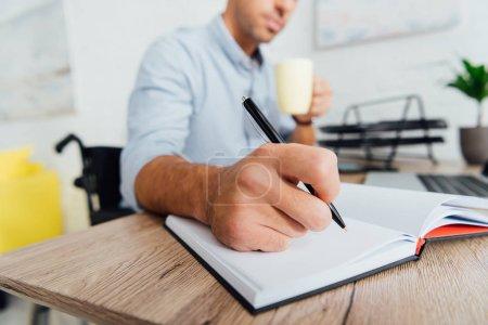 Photo pour Focus sélectif de l'homme en fauteuil roulant tenant la tasse et l'écriture dans le carnet de notes au bureau - image libre de droit