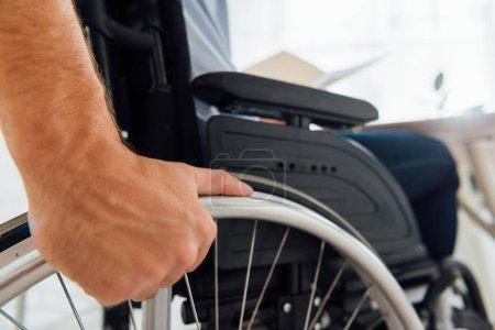 Photo pour Gros plan de l'homme tenant la roue du fauteuil roulant - image libre de droit