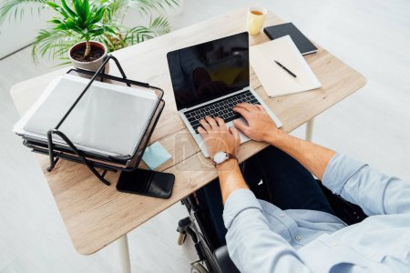 Photo for Cropped view of man in wheelchair using laptop with blank screen at workplace - Royalty Free Image