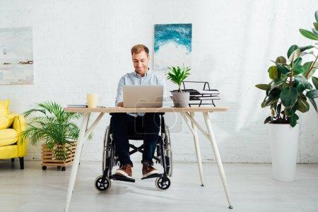 Photo pour Freelance souriant en fauteuil roulant en utilisant un ordinateur portable au bureau dans le salon - image libre de droit