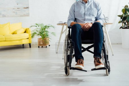 Photo for Cropped view of man sitting in wheelchair in living room - Royalty Free Image