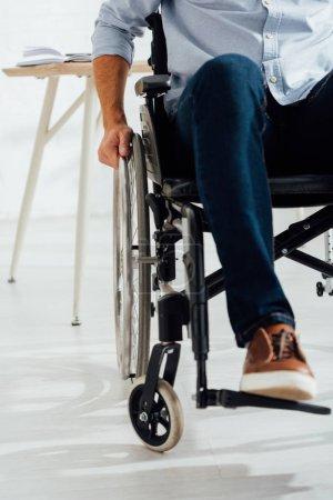 Photo pour Vue en plan de l'homme tenant la main sur la roue du fauteuil roulant - image libre de droit