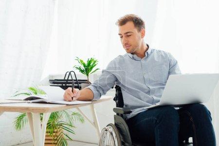 Photo pour Homme d'affaires en fauteuil roulant tenant un ordinateur portable et écrivant dans un carnet au bureau - image libre de droit