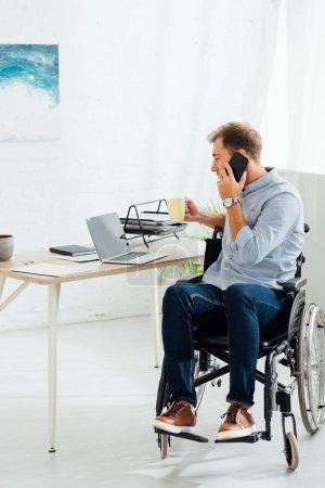 Photo pour Homme en fauteuil roulant parlant sur smartphone et tenant tasse de café sur le lieu de travail - image libre de droit