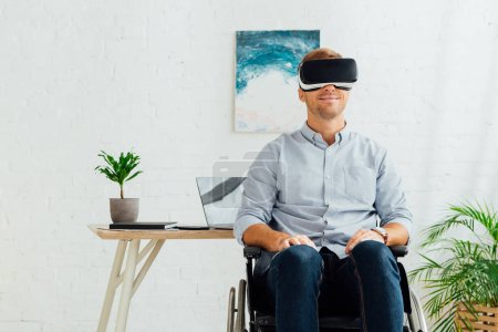 Photo for Smiling disabled man in wheelchair using virtual reality headset in living room - Royalty Free Image