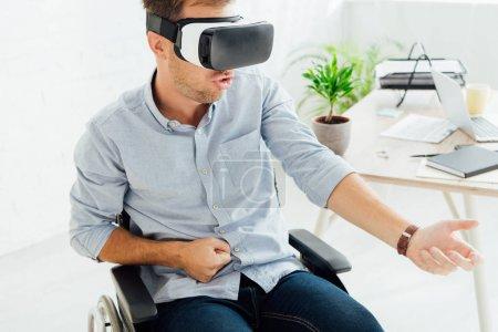 Photo pour Homme excité en fauteuil roulant utilisant casque de réalité virtuelle par lieu de travail - image libre de droit