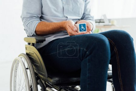Photo for Cropped view of man in wheelchair holding cube with disabled sign - Royalty Free Image