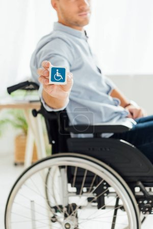 Photo for Cropped view of man in wheelchair showing cube with disabled sign - Royalty Free Image