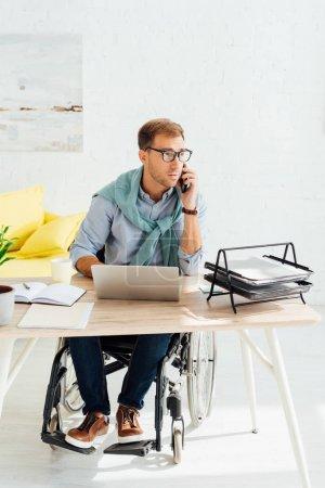 Photo pour Homme en fauteuil roulant parlant sur smartphone tout en travaillant sur ordinateur portable - image libre de droit