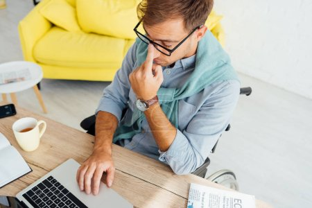 Man in wheelchair adjusting eyeglasses while using notebook at workplace