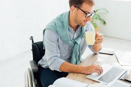 Photo pour Homme d'affaires occasionnel en fauteuil roulant utilisant des écouteurs sans fil et un ordinateur portable tout en tenant la tasse - image libre de droit