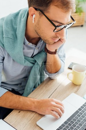 Photo for Freelancer with hand on chin using wireless earphones and laptop at working desk - Royalty Free Image