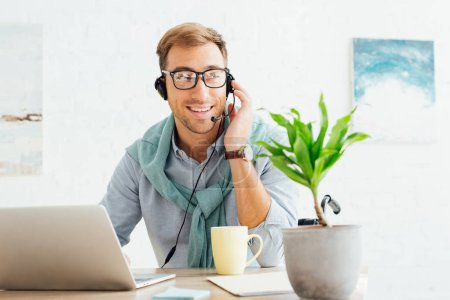 Smiling call center operator in wheelchair talking on headset at workplace