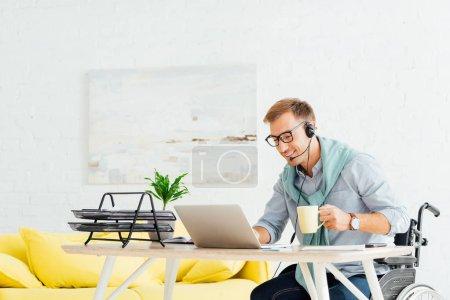 Photo pour Homme en fauteuil roulant utilisant un casque, travaillant sur un ordinateur portable et tenant la tasse dans le salon - image libre de droit