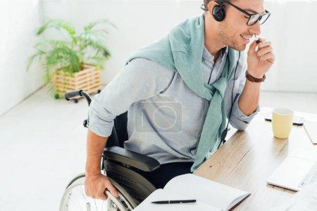 Photo pour Opérateur de centre d'appels souriant en fauteuil roulant parlant sur un casque d'écoute - image libre de droit