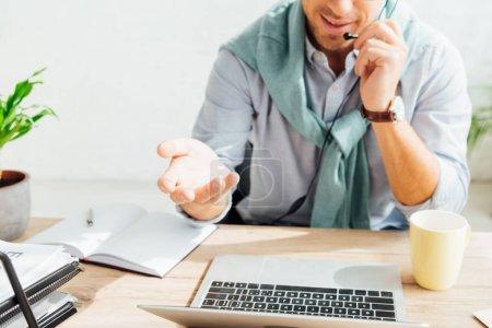 Photo pour Vue agrandie de l'opérateur du centre d'appels dans le casque d'écoute sur le lieu de travail - image libre de droit