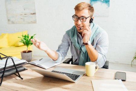 Photo pour Opérateur de centre d'appels souriant dans le casque travaillant dans le salon - image libre de droit