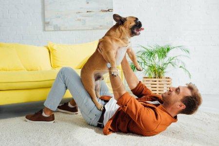Photo pour Vue latérale d'un homme jouant avec un taureau français sur un tapis à la maison - image libre de droit