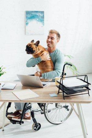Photo pour Homme souriant en fauteuil roulant tenant un bouledogue français à la maison - image libre de droit
