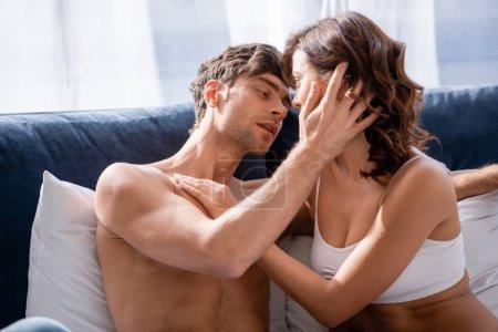 Photo pour Beau copain embrassant et embrassant petite amie en sous-vêtements blancs - image libre de droit