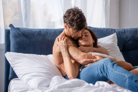 Photo for Handsome boyfriend hugging attractive girlfriend with closed eyes in bed - Royalty Free Image