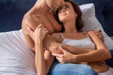 Photo pour Vue recadrée de copain étreignant petite amie en sous-vêtements au lit - image libre de droit