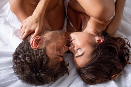Photo pour Top view of girlfriend and boyfriend kissing and hugging in bed - image libre de droit