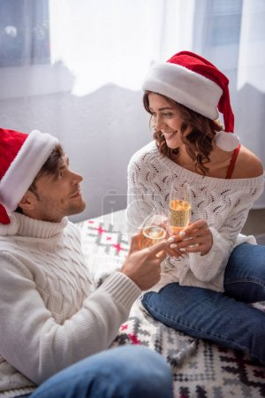 Photo for Boyfriend and smiling girlfriend in santa hats clinking with champagne glasses at christmastime - Royalty Free Image