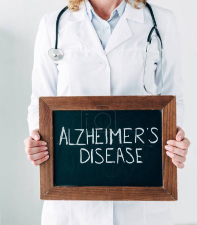 Photo for Cropped view of doctor in white coat holding wooden board with lettering Alzheimer disease - Royalty Free Image