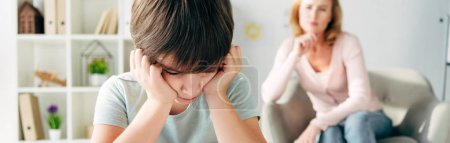 Photo for Panoramic shot of sad kid with dyslexia and child psychologist on background - Royalty Free Image