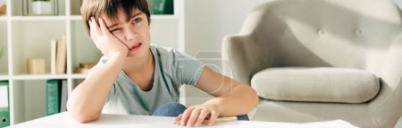 Photo for Panoramic shot of pensive kid with dyslexia sitting at table - Royalty Free Image